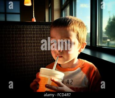 Close-Up Portrait Of Cute Boy Drinking While Sitting In Restaurant - Stock Photo