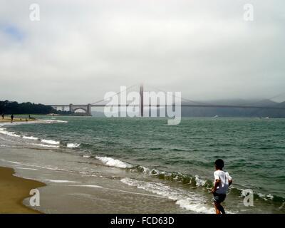 Boy Walking On Beach, Suspension Bridge In Background - Stock Photo