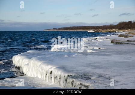 Ice covered flat rock coast at the swedish island Oland in the Baltic Sea - Stock Photo