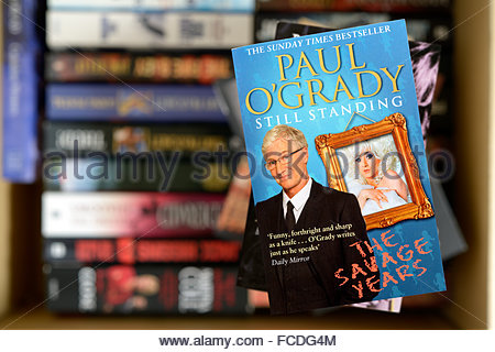 Paul O'Grady 2012 autobiography Still Standing, stacked used books, England - Stock Photo