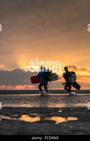 Netherlands, Ouddorp, Beach near Brouwersdam, part of Deltaworks. Kitesurfers going home - Stock Photo