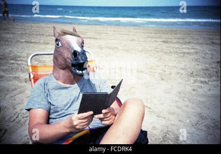 Man In Horse Head Reading Book On Beach - Stock Photo