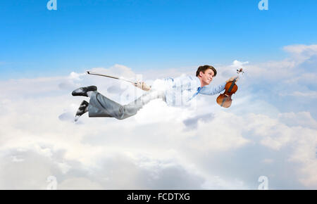 Young businessman flying in sky and playing fife - Stock Photo