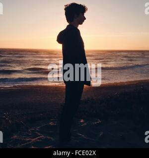 Side View Of Man Standing On Beach Against Sky - Stock Photo