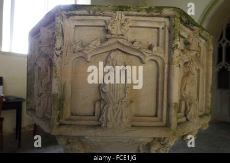 Detail from the 15th century stone font with carvings of the apostles, St Peter, St Nicholas Church, Buckenaham - Stock Photo