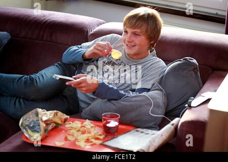 France teenager eating and watching TV - Stock Photo