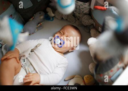 8 months baby boy crying in his bed - Stock Photo