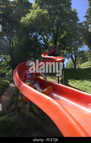 Cute Little Boy On Slide Against Trees - Stock Photo