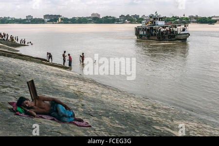 A homeless man asleep, people bathing, and a public ferry as it crosses the Hooghly to Howrah. - Stock Photo