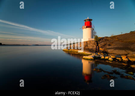 Lighthouse on the rocky coast in the Swedish island Yxlan in the archipelago near Stockholm at sunset - Stock Photo
