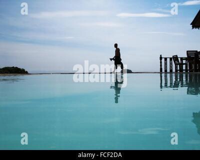 Silhouette Of Man Walking On Water - Stock Photo