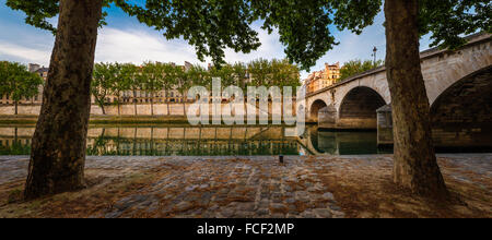 Ile Saint Louis and Pont Marie with the Seine River banks lined with aspen trees on a quiet morning in Paris, France - Stock Photo
