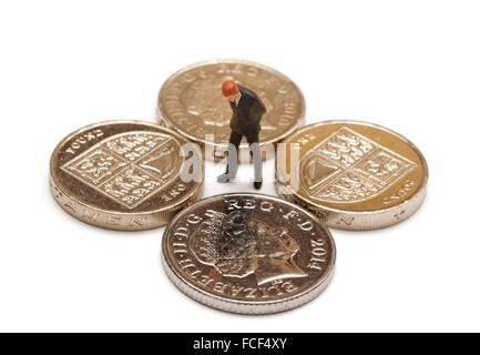 A Miniature figurine man in a suit looking at one pound coins and a ten pence piece - Stock Photo
