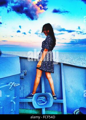 Full Length Of Young Woman On Boat Against Sky - Stock Photo
