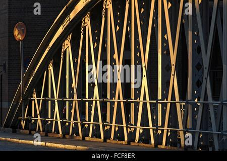 The riveted iron network of the cultural monument Neuerwegsbrücke in Hamburg's warehouse district in the evening - Stock Photo