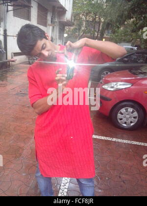 Young Man Photographing Through Smart Phone At Parking Lot - Stock Photo
