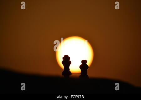 Silhouette King And Queen Chess Pieces Against Orange Sky - Stock Photo