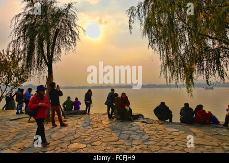 Chinese People watching sunset at Summer place of Empress Dowager near Beijing; China - Stock Photo