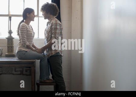 Loft living. A couple facing each other holding hands. - Stock Photo
