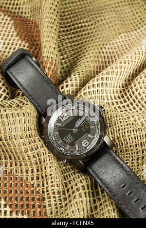Men's Watch Chronograph on camouflage netting - Stock Photo