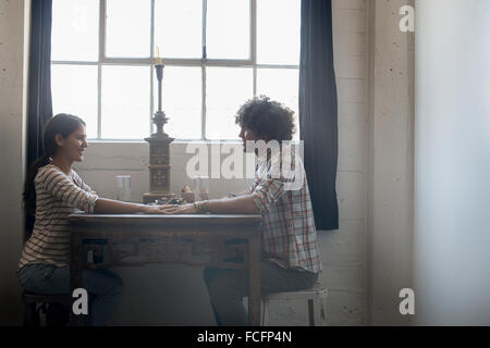 Loft living. A couple sitting facing each other holding hands across a table. - Stock Photo