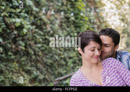 A couple in a city park beside a green wall of foliage embracing. - Stock Photo