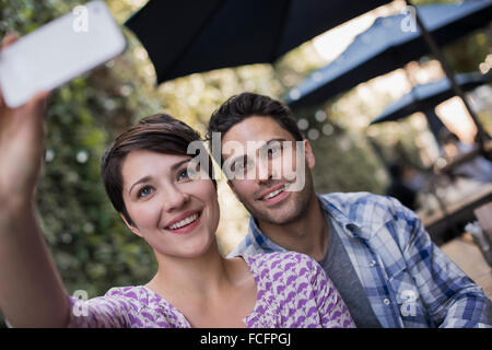 A couple seated at an outdoor city cafe, taking a selfy with a smart phone. - Stock Photo