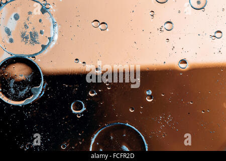 Oil drops on a water surface with color background - Stock Photo