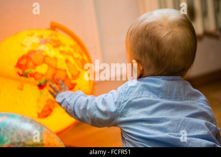 young child with lighting globe, boy and yellow ball - Stock Photo