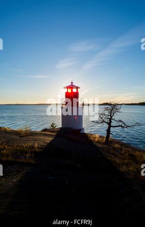Sunrays shine through a lighthouse on the rocky coast in the Swedish island Yxlan in the Archipelago near Stockholm - Stock Photo