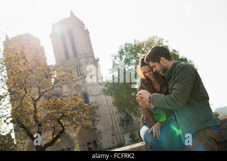 A couple side by side looking a a smart phone screen outside Notre Dame cathedral in Paris. - Stock Photo