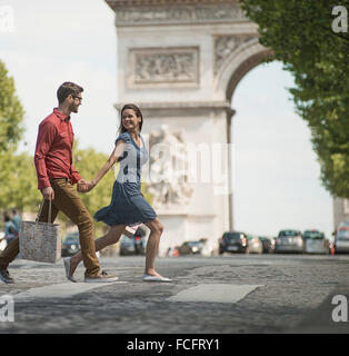 A couple hand in hand carrying shopping bags and crossing the road - Stock Photo