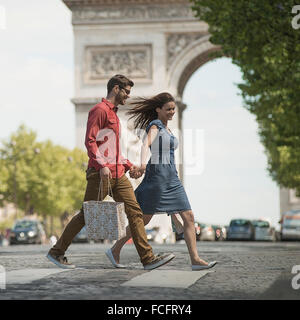 A couple hand in hand carrying shopping bags and crossing the road in a European city. - Stock Photo