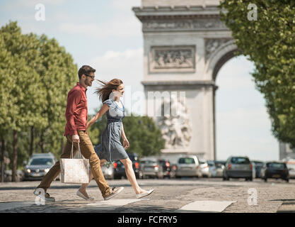 A couple hand in hand carrying shopping bags and crossing the road by a historic monument - Stock Photo