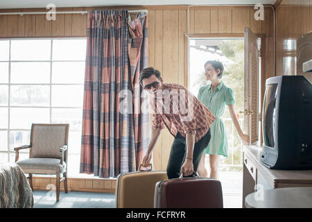 A young couple arriving in a motel room. - Stock Photo