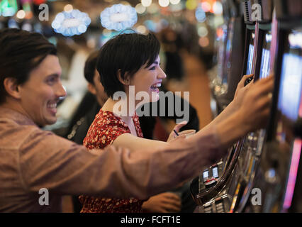 Two people, a young man and woman, playing the slot machines in a casino. - Stock Photo