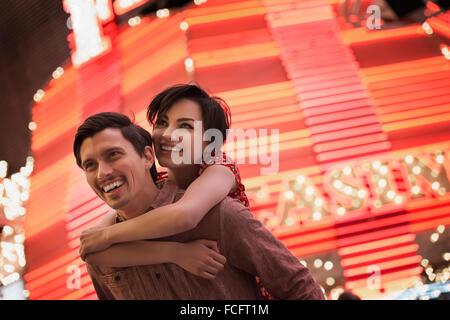 A man giving a woman a piggyback, under a bright neon Casino sign. - Stock Photo