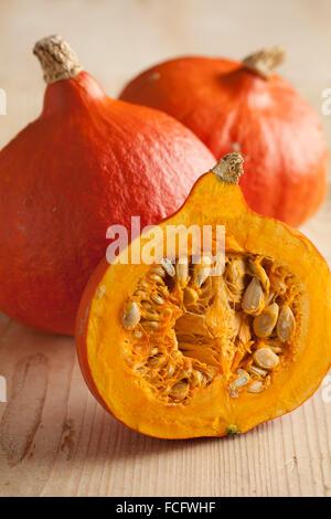 Fresh ripe orange whole and half hokkaido pumpkin - Stock Photo