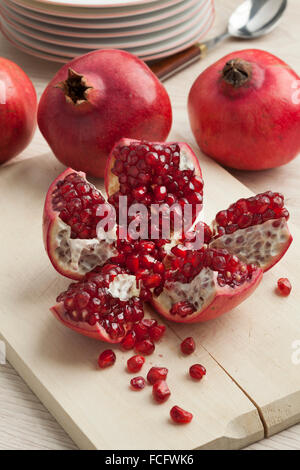 Open fresh red ripe pomegranate fruit and seeds - Stock Photo