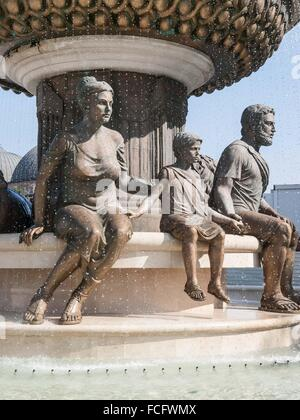 Large water fountain and bronze sculptures of adults and children in Skopje, Macedonia, Europe. - Stock Photo
