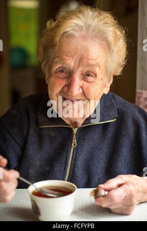 Elderly woman drinking tea in the kitchen. - Stock Photo