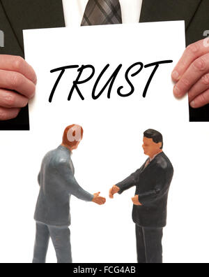 Trust concept  2 miniature figurines in suits shaking hands - Stock Photo