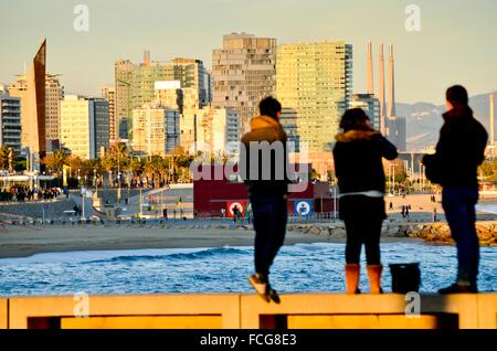 Silhouette of three people back contemplating a coastal cityscape. Beach and sea. Buildings and skyscrapers skyline. - Stock Photo