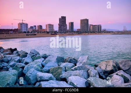 Breakwater, beach and Diagonal Mar buildings on the horizon at sunset. Barcelona, Catalonia, Spain. - Stock Photo