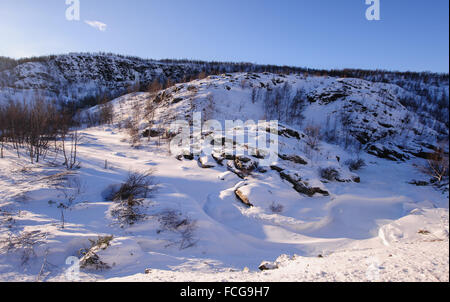 Winter landscape in northern Norway with a frozen river, birch trees and mountains under a blue sky with clouds - Stock Photo