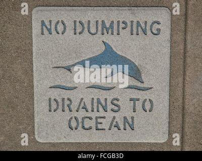 Sign on sidewalk that says No Dumping Drains to Ocean with a picture of a dolphin in Los Angeles California. - Stock Photo