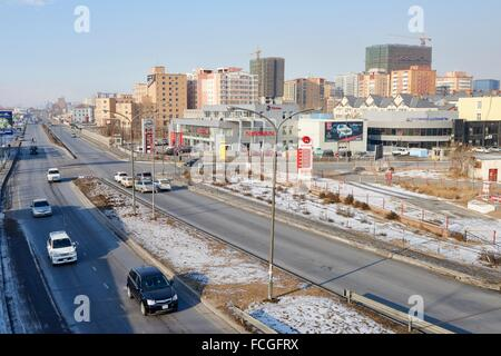Vehicles along Narnii Road, a busy commercial area in Sukhbaatar District. In the background a newly built residential - Stock Photo