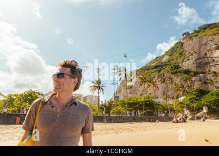 Brazil Morro da Urca behind a male tourist on Praia Vermelha in Rio de Janeiro - Stock Photo