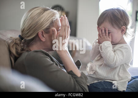 Mother and baby girl playing at home - Stock Photo