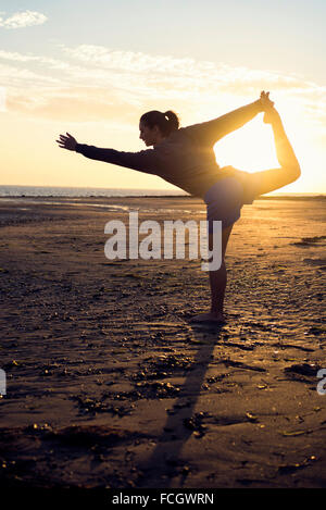 Spain Puerto Real silhouette of young woman doing yoga on the beach at sunset - Stock Photo